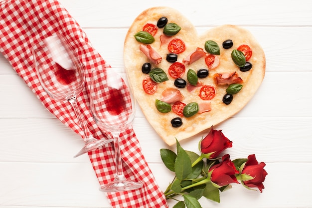Top view heart shaped pizza with wine