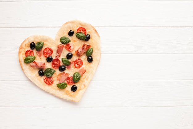 Top view heart shaped pizza on wooden table