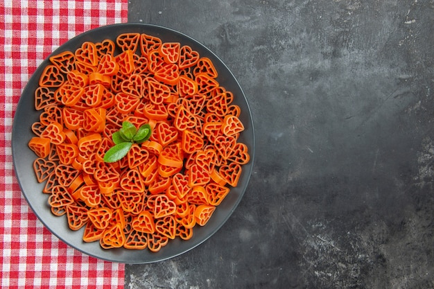 Top view heart shaped red italian pasta on black oval plate on kitchen towel on dark table with free space
