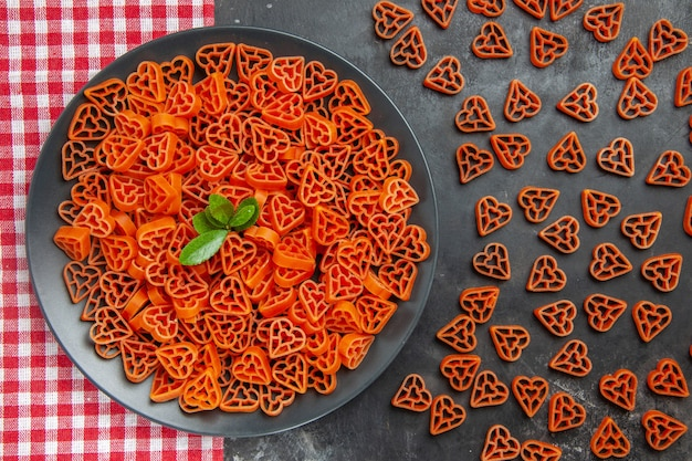 Top view heart shaped red italian pasta on black oval plate on kitchen towel scattered red heart pasta on dark table
