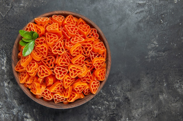 Top view heart shaped red italian pasta in a bowl on dark table with free space