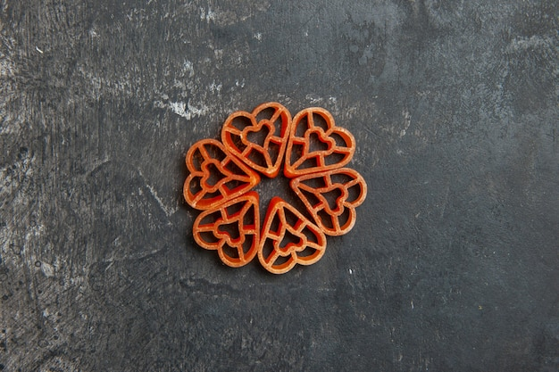 Top view heart shaped red italian pasta on dark table with copy place