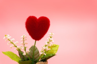 Top view Heart-shaped red tree in a small sack tied with rope on pink background