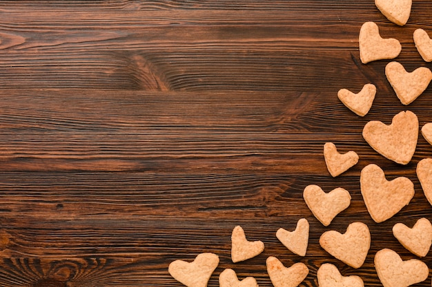 Top view of heart-shaped valentines day cookies on wooden background