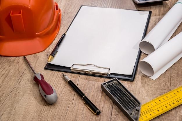 トップビューヘルメット、空白の建築図面、コンパスの描画、木製のテーブルのツールを描画します。