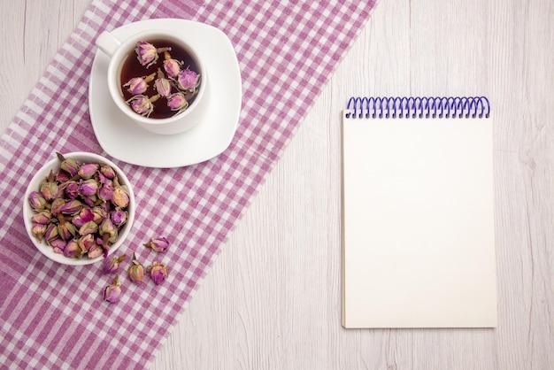 トップビューハーブティー市松模様のテーブルクロスとテーブルの上の白いノートのハーブのボウルの横にある受け皿にハーブティーのカップ
