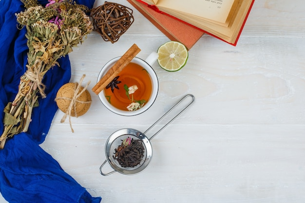 Top view herbal tea, cookies and flowers with books, lemon, tea strainer and spices on white surface