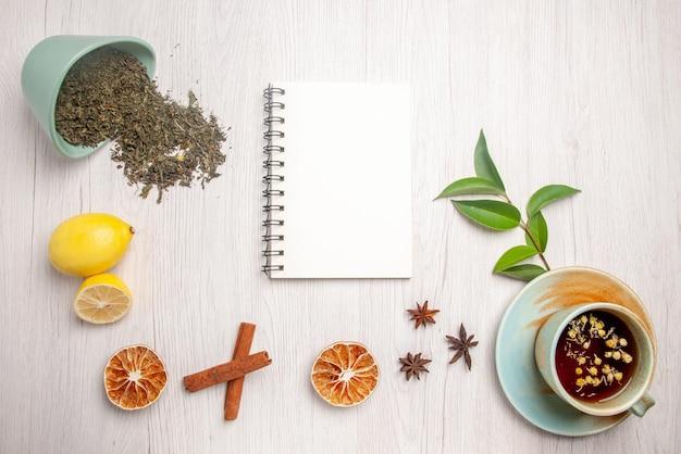 Vista dall'alto tisana tisana nella tazza bianca accanto al quaderno bianco limone anice stellato bastoncini di cannella erbe sul piatto bianco