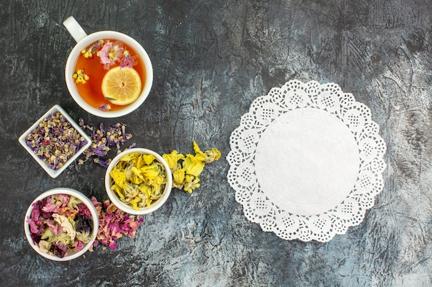 Top view of herbal tea near bowls of dry flowers with a piece of white lace on grey ground