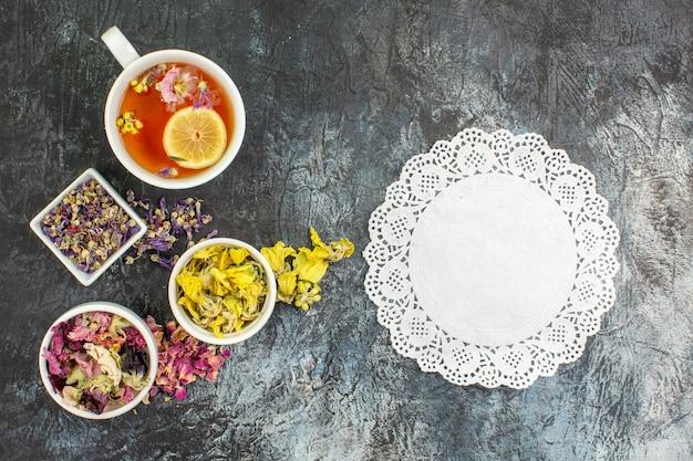 Vista dall'alto della tisana vicino a ciotole di fiori secchi con un pezzo di pizzo bianco su fondo grigio