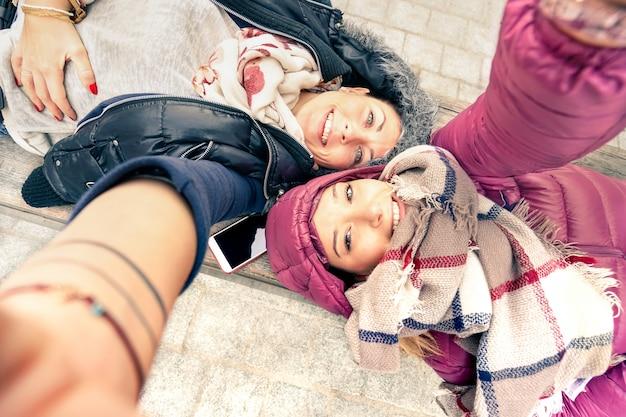 Top view of hipster girlfriends taking selfie