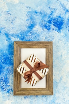 Top view holiday gift on empty photo frame on blue white grunge copy place