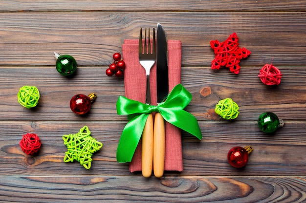 Top view of holiday set of fork and knife on wooden surface