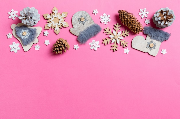 Top view of holiday toys and decorations on pink christmas.