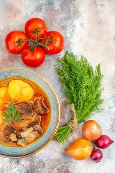 Vista dall'alto zuppa di bozbash fatta in casa un mucchio di cipolle pomodori aneto su sfondo nudo