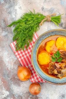 トップビュー自家製ボズバッシュスープキッチンタオルヌードの背景にディル玉ねぎの束