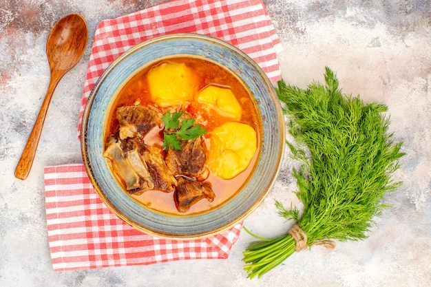 トップビュー自家製ボズバッシュスープキッチンタオルヌードの背景にディルスプーンの束