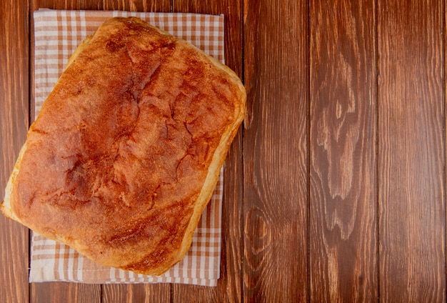 Top view of homemade bread on plaid cloth and wooden background with copy space