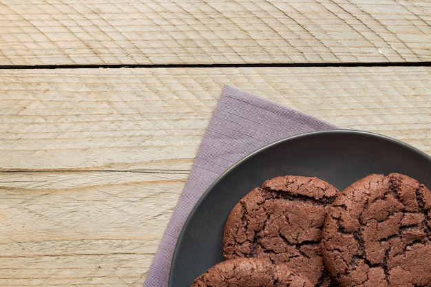 Top view of homemade chocoate cookies on black plate on wooden background. home bakery