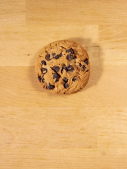 Top view of homemade chocolate chip cookie on a wooden table