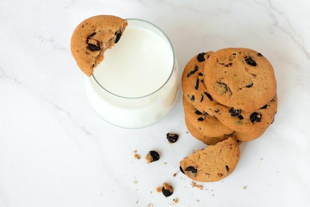 大理石の背景に自家製チョコレートチップクッキーとミルクのガラスの上面図