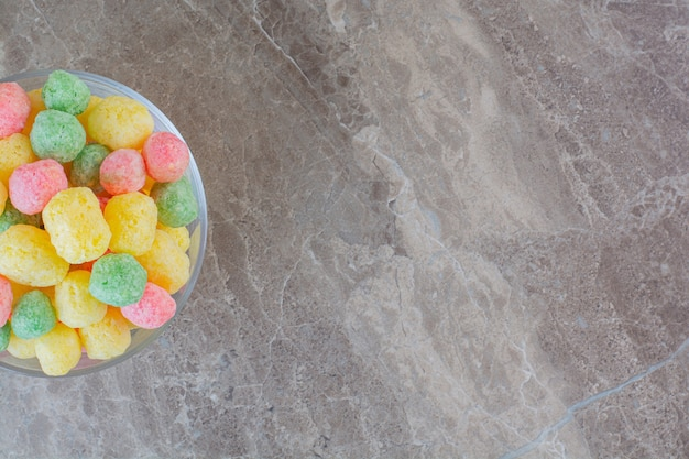 Top view of homemade colorful candies in bowl over grey.