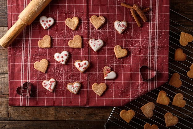 Top view homemade cookie hearts with frosting on burgundy cloth towel on wooden background