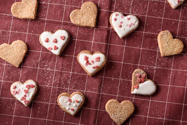 バレンタインデーのためのブルゴーニュの布ナプキンのフロスティングとトップビュー自家製クッキーハート