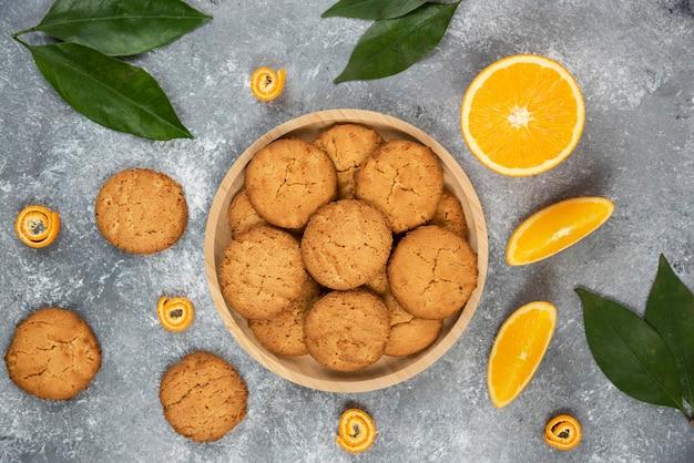 회색 탁자 위에 오렌지 조각과 잎이 있는 나무 판자 위에 홈메이드 쿠키가 있습니다.
