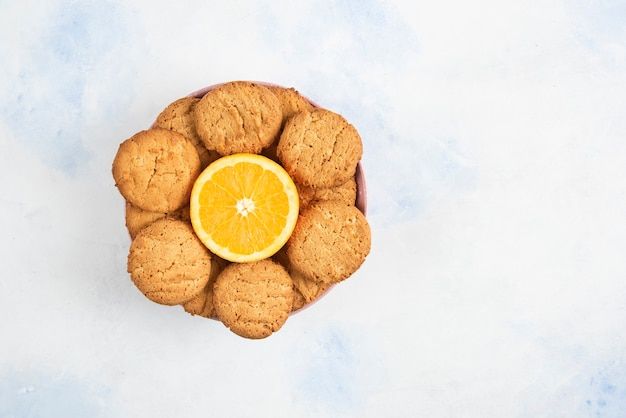 Top view of homemade cookies with half cut orange in bowl over white table.