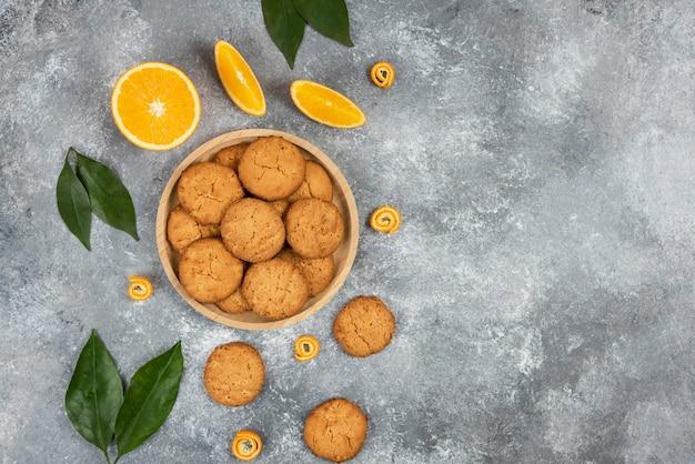 Vista dall'alto di biscotti fatti in casa su tavola di legno e arance con foglie su superficie grigia. illustrazione di alta qualità
