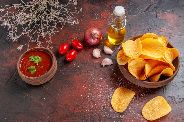 Top view of homemade delicious crispy potato chips inside and outside of brown pot oil bottle ketchup tomatoes garlic onion on dark background