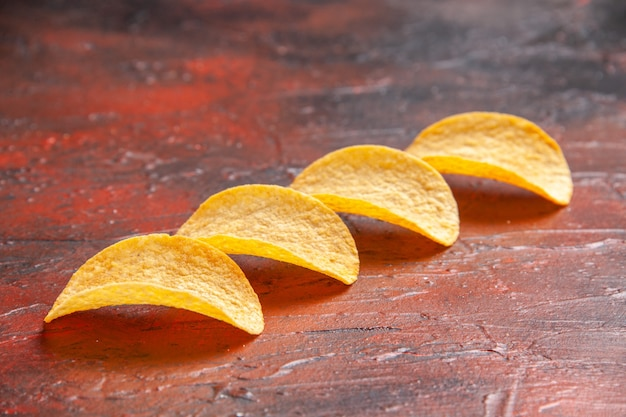 Top view of homemade delicious four crispy chips lined up on dark background