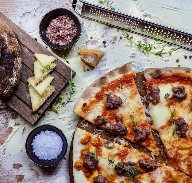 Vista dall'alto di una deliziosa pizza fatta in casa su un tavolo da cucina