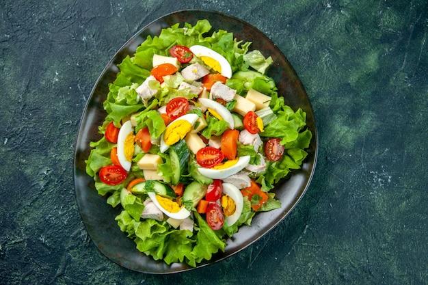 Vista dall'alto di deliziosa insalata fatta in casa in un piatto nero su sfondo di colori mix nero verde con spazio libero