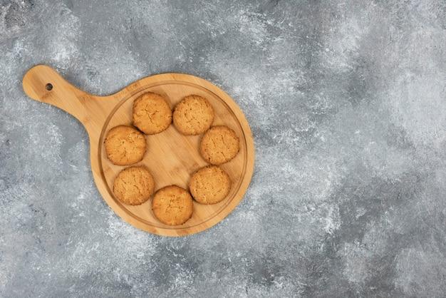Vista dall'alto di biscotti freschi fatti in casa su tavola di legno su superficie grigia.
