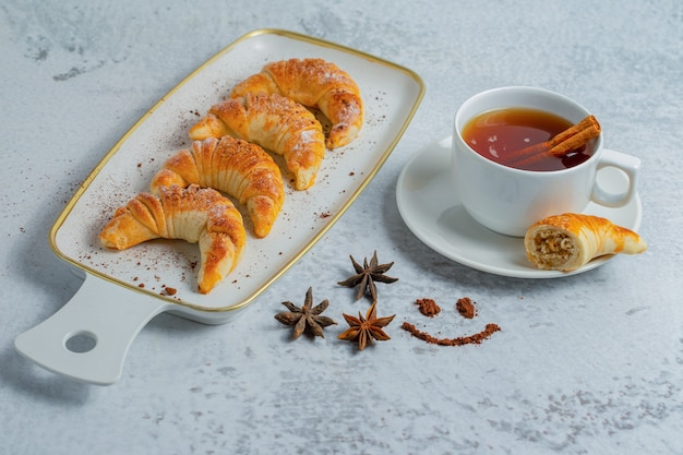 Vista dall'alto di croissant freschi fatti in casa con tè fresco su superficie grigia.