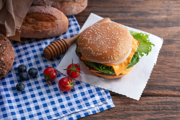Top view of homemade hamburger with fresh vegetables on paper and breads