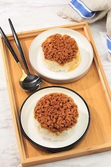 上面図自家製ナシティムアヤム、さいの目に切ったチキン醤油とご飯。朝食のためのインドネシアのコンフォートフード。テキスト用のコピースペースを備えたセラミックプレートで提供