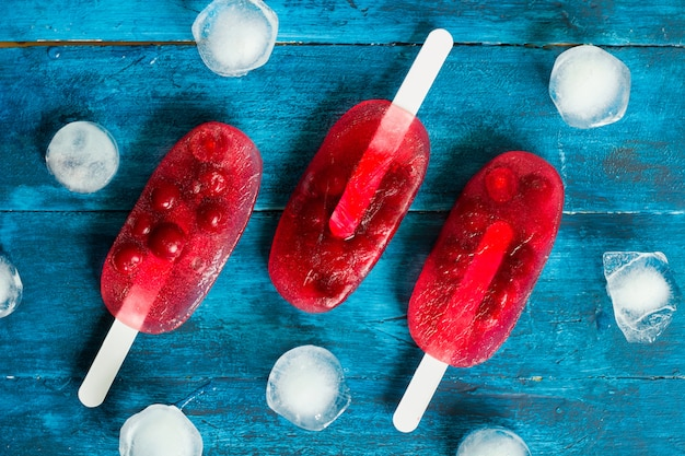 Top view homemade red cherry ice cream on a blue wooden background