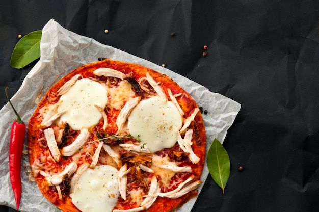 Top view of homemade thin fresh italian pizza served on paper and black background