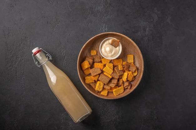 ボトルと暗い木製のクラッカーでトップビュー自家製の伝統的なロシアの軽いライ麦kvass