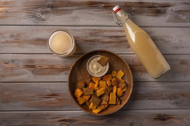 トップビューガラスカップと木製のクラッカーの瓶の中の自家製の伝統的なロシアの軽いライ麦kvass
