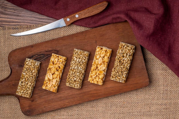 Top view of honey bars with peanuts sesame and sunflower seeds on a wooden board on rustic