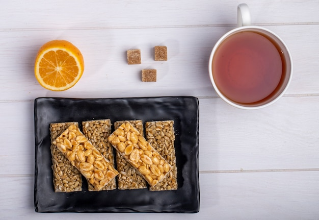 Top view of honey bars with peanuts and sunflower seeds on a black platter with a cup of tea and lemon on white