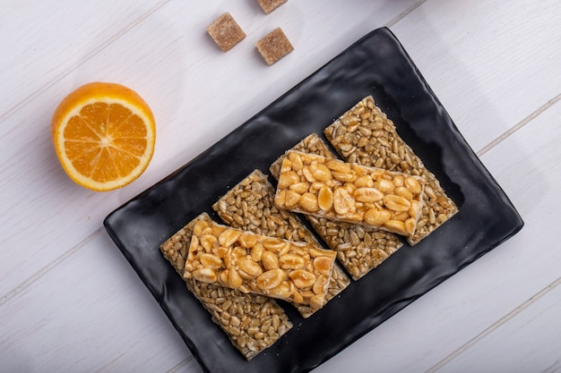 Top view of honey bars with peanuts and sunflower seeds on a black platter with orange on rustic