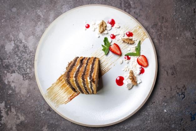 Вид сверху медовик на белой тарелке на бетонном фоне
