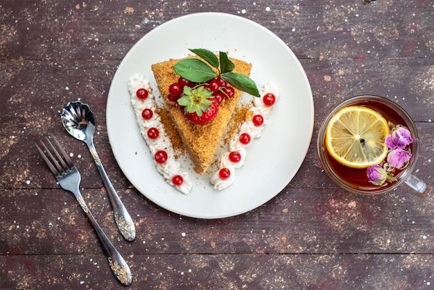 Una fetta di torta di miele vista dall'alto con mirtilli rossi all'interno del piatto bianco con tè sul tè torta sfondo scuro