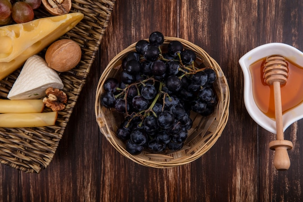 木製の背景の上のスタンドにブドウ品種のチーズとナッツとソーサーのトップビュー蜂蜜