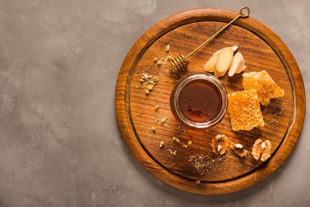 Вид сверху банку меда с едой и медовой ложкой